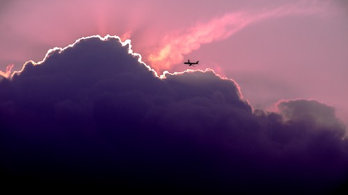 plane flying into dark clouds during a colorful sunset